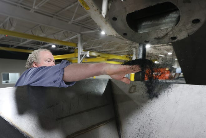 Bryan Eagle, president and CEO of Memphis-area startup Glanris, reaches out to grab some of the company's produced carbon from rice hulls inside their new 60,000 square foot facility in Olive Branch on Wednesday, Aug. 25, 2021.