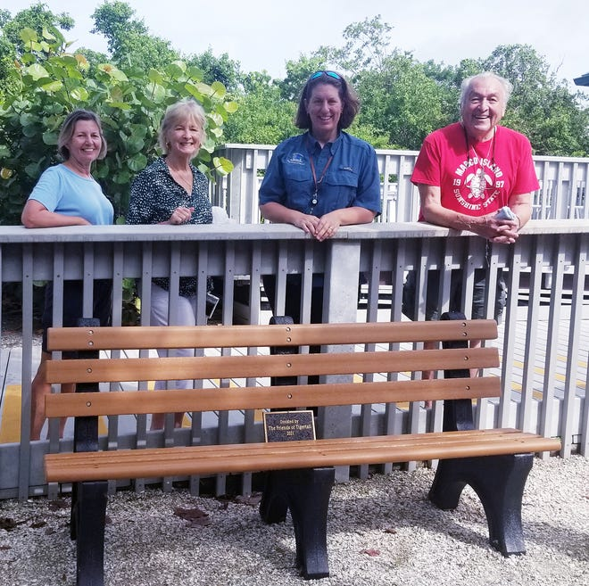 Friends of Tigertail board members Allie Delventhal, Linda Colombo, and Russ Colombo stand with Melissa Hennig behind the new bench in the playground area.