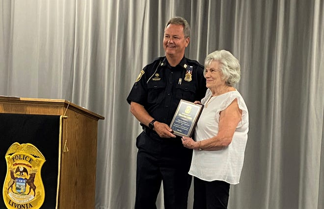 Marry Ann Schils, right, with Livonia police Capt. Thomas Goralski.