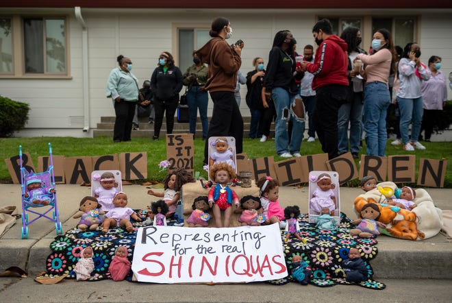 21 Black baby dolls are placed next to a sign that reads, 'Representing for the real Shiniquas' on the sidewalk of the the Salinas Union High School District office in Salinas, Calif., on Tuesday, Aug. 24, 2021. This was in response about last Friday's  incident where Salinas High School students defaced a Black baby Doll.