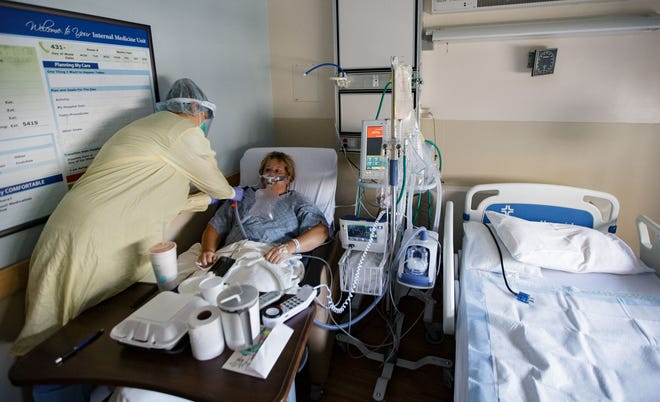 Jaclynn Moss, RN Nurse Manager of Internal Medicine at Tallahassee Memorial HealthCare, adjusts a tube connected to COVID patient, Tanya English's oxygen mask Monday, Aug. 23, 2021.