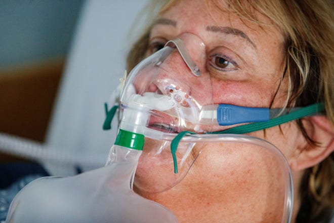 """Tanya English, 60, uses an oxygen mask to breathe as she sits in a chair in her hospital room on the floor of the yellow level COVID unit Monday, Aug. 23, 2021. Before agreeing to have her picture taken, English said, """"If it means I help one person, then I'll do it."""""""