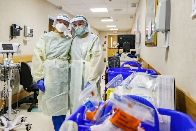 Sally Fowler, 21, and her best friend Emily Brown, 23, who are both nurses working in the yellow level COVID unit at Tallahassee Memorial HealthCare, pose for a photo in the hallway of the unit, which is lined with medical supplies and computers Monday, Aug. 23, 2021.