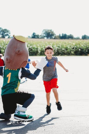 Spudly dishes out a high-five to a young runner in the Alsum Farms & Produce annual Fall Festival and Tater Trot 5K Run and 2 Mile Walk.