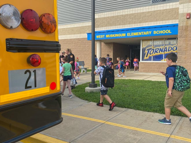 Student hop off the bus on their way to being the 2021 through 2022 school year at West Muskingum Elementary.