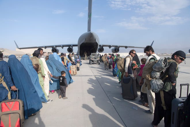 In this image provided by the U.S. Air Force, U.S. Air Force loadmasters and pilots assigned to the 816th Expeditionary Airlift Squadron, load people being evacuated from Afghanistan onto a U.S. Air Force C-17 Globemaster III at Hamid Karzai International Airport in Kabul, Afghanistan, Tuesday.