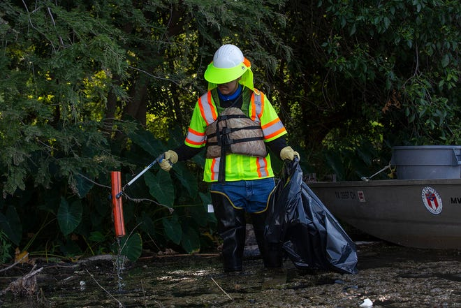 Watershed protection crew member Edgar Diaz picks up trash on Lady Bird Lake in late August. With an abnormal amount of rain this summer, Austin officials are also seeing an increase in the frequency of trash being blown into Lady Bird Lake.