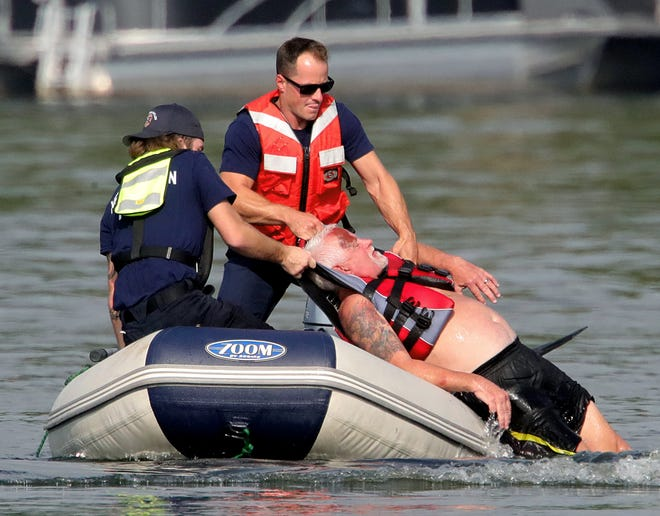 Ryan Henry, left, and Adam Guillod of the New Franklin Fire Department lift Bob Stokes into their raft as they work a boat crash training drill Thursday on Turkeyfoot Lake in New Franklin.