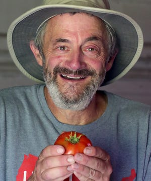 Randy Katz shows off an heirloom tomato that he grew on his 3½-acre farm in Copley for Vacarro's Trattoria.