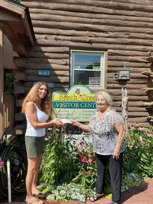 Town & Country Garden Club of Alliance President Cindy Wahl, right, presents a check to Melinda Carmichael of Beech Creek Botanical Garden.