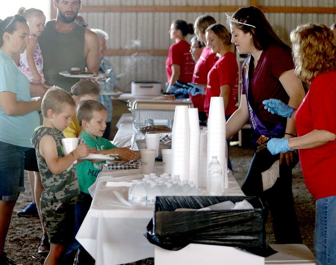 Guests pick up plates of freshly made sausage and pancakes Saturday, Aug. 21, 2021, during a community breakfast organized by the Ohio Farm Bureau at Maple Valley Farm in Knox Township.