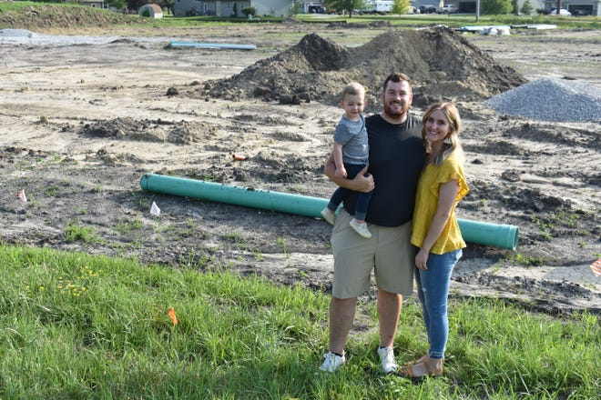 Matt and Marianne Pacha and their son Warren pose at the construction site of their new restaurant, Flight Bar + Grille, along Highway 69 in north Huxley.