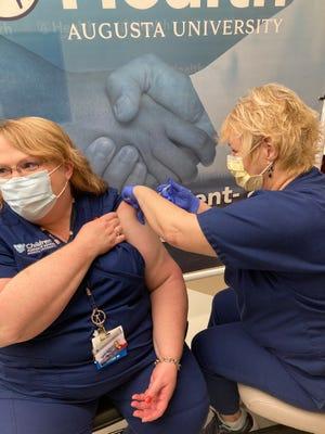 AU Health System nurse Leslie Slantis, left, receives a COVID-19 vaccine booster shot from Employee Health nurse Phyllis Hallman during an employee vaccination clinic Thursday.