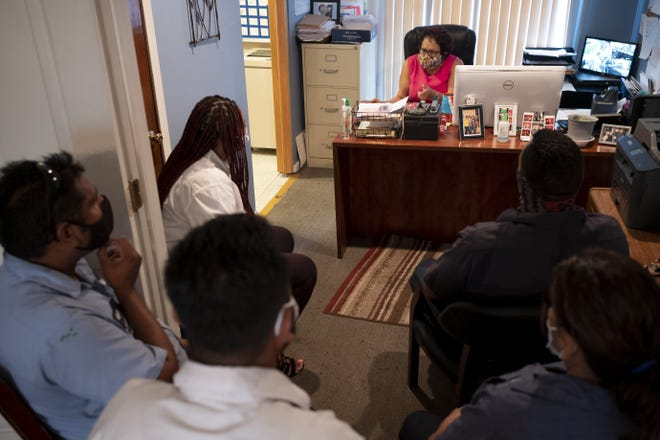 Anamaria Perales-Lang, center, director of Belle Harbour Management, leads a morning staff meeting at Manchester Townhomes.