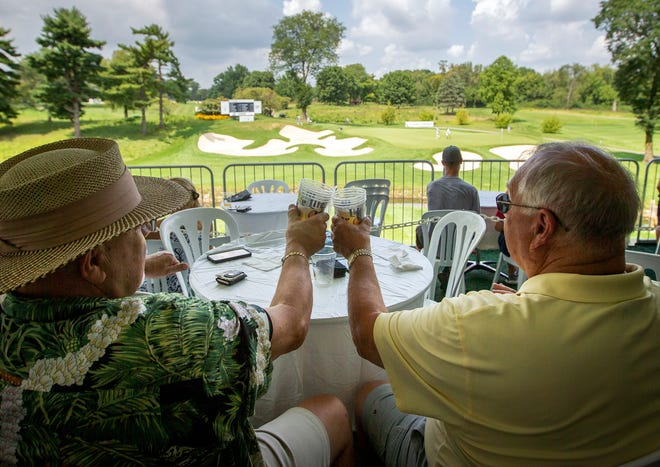 Ernie Tuller, left, and Ed Tumulty, neighbors from Dublin, cheers after a birdie by Brad Hopfinger on Thursday at Pub Thirteen at the Nationwide Children's Championship.