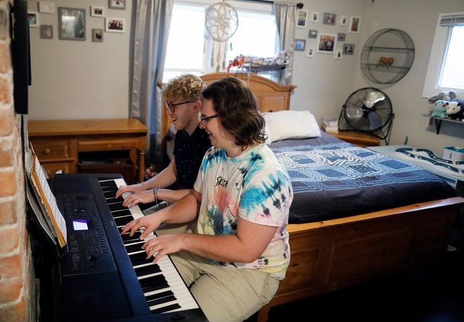 """Philip Baltzer, in the forefront, and his boyfriend Nick Mayes play the piano in the bedroom of their South Side home. Both Baltzer and Mayes are music teachers. Baltzer, 24, said he recently realized he'd been through conversion therapy by a local pastor after watching the Netflix documentary """"Pray Away."""""""