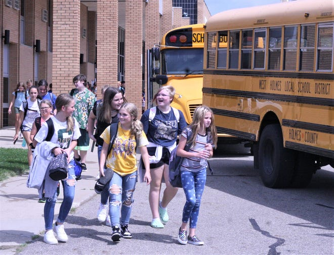 West Holmes Middle School students head for their buses Thursday afternoon after finishing their school day. West Holmes is one of five districts in the tri-county area that is not requiring masks to be worn on buses as the new school year begins, despite the federal mandate.