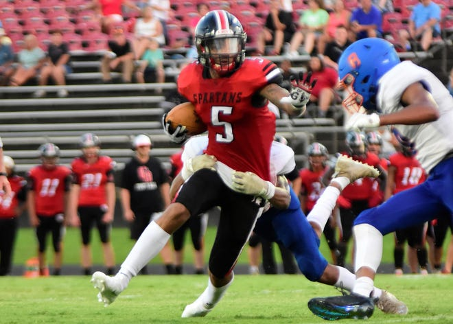 Central Davidson's Jaylyn Smith tries to escape a Lexington tackle in the Spartans' season-opener last Friday. [David Yemm for the Dispatch]