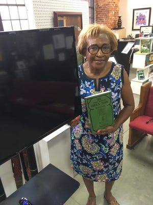 """African American Museum of History and Culture curator Dot Guthrie holds a copy of  """"The Green Book."""""""