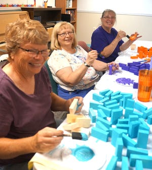 Pam Schmidtberger of Victoria, Patti Curlile, and Linda Collins, both of Hays, paint wooden blocks that will be packed into Operation Christmas Child shoeboxes. The painting event, held recently at North Oak Community Church in Hays, was in preparation for the church's Sunday School shoebox packing party later this fall. A workshop for OCC volunteers will be held Saturday, Sept. 11.