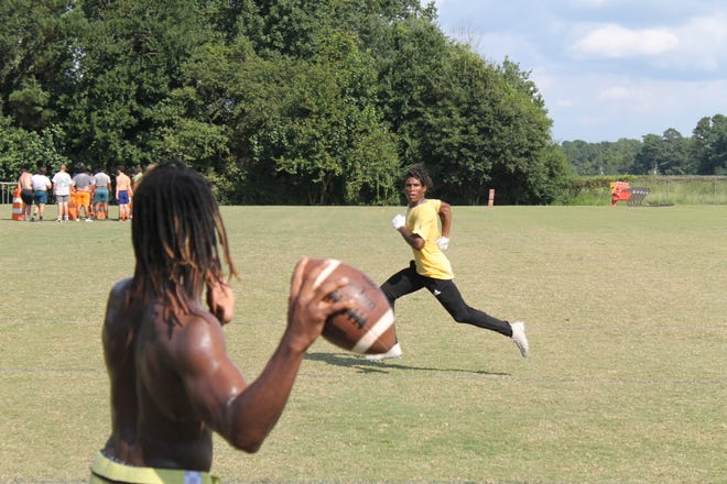 Robert Cobb prepares to fire a pass to his brother Joseph Cobb during South Lenoir football practice. The brothers are hoping to bring some success to South Lenoir in their final season playing together.