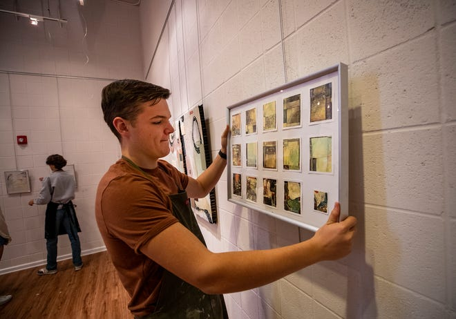 Harrison Arts student Nick Burgess hangs his mixed media artwork in the Harrison Gallery for a show that opens Tuesday in Lakeland. The annual art show is a celebration of high scoring advanced-placement student portfolios from across Polk County.