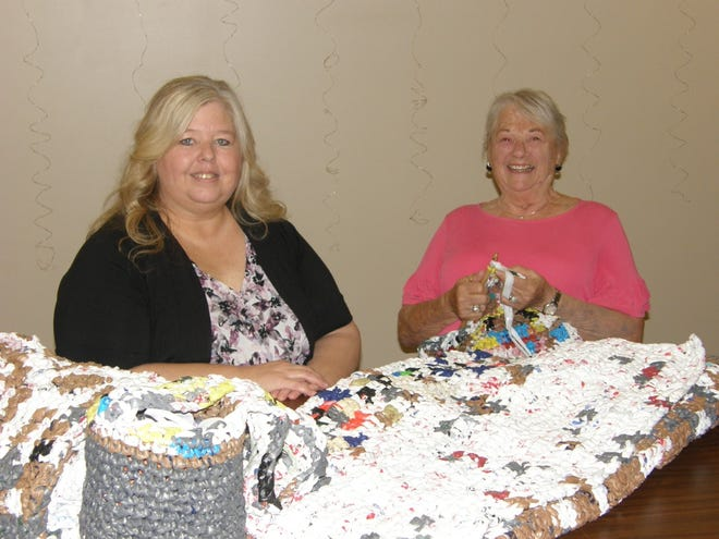Crystal Martin, executive director of Family Counseling Shelter Services of Monroe County (left), gets a quick crochet lesson from Andrea Johnson of Monroe. Johnson, along with women of Trinity Episcopal Church and members of the community, work on recycling projects using ordinary plastic grocery bags.
