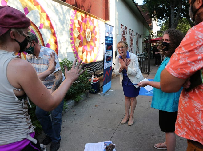 Artist Katie Runde greets Sen. Maggie Hassan, D-NH, with her hands covered with chalk dust after she completes her mural installation in Portsmouth advocating for a national paid family and medical leave policy on Wednesday, Aug. 25, 2021.