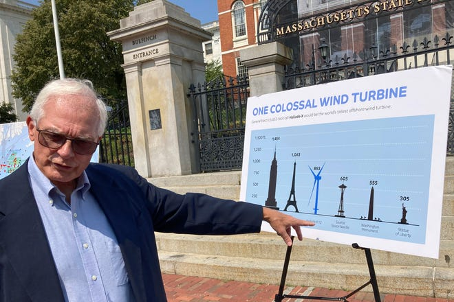 David Stevenson, policy director at the Caesar Rodney Institute, a group that opposes wind-power projects, points to a placard that features images of landmarks and a wind turbine as he talks with reporters at the Massachusetts State House on Wednesday.
