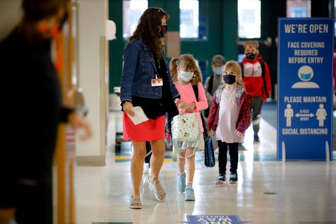 In this Wednesday, Sept. 16, 2020, file photo, kindergarten students wear masks as they are led into Lee Elementary School, in Lee, Mass. The Massachusetts Board of Elementary and Secondary Education on Tuesday, Aug. 24, 2021 overwhelmingly approved a measure that gives state Education Commissioner Jeff Riley the authority to issue a universal mask mandate for the state's K-12 schools.