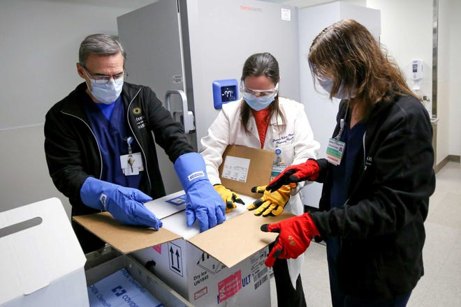 Health-care workers unpack COVID-19 vaccine that arrived at Rhode Island Hospital in January.