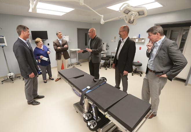 Ascent Family Surgery Center co-owners, from left Dr. Darrell Smith , Dr. Aaron Brescia, Dr. Charles Bogdan and Dr. Kent Ramsey, lead a tour of one of the facilities operating rooms for Debra Brescia, second from left, and Dr. Stan Anderson, far right, during a recent open  house. The center is set to open in September.