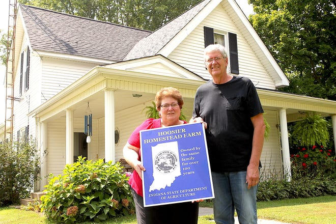 """June and Jerry Fountain pose for a picture in front of their house Wednesday afternoon. June is holding a sign from the state, which is the """"Hoosier Homestead"""" award, recognizing the farm for being in the same family for 100 years."""