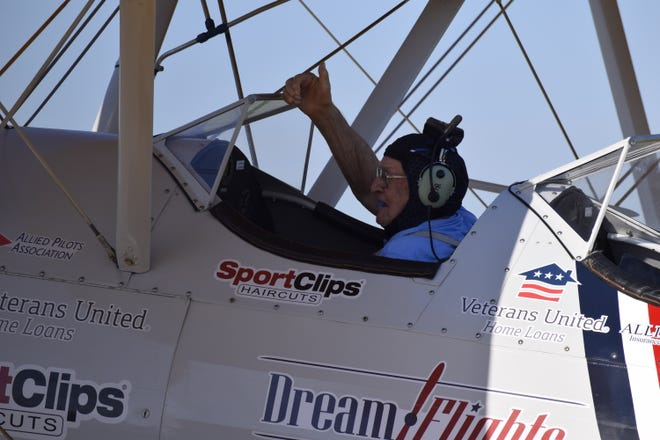 Bob Cook gives a thumbs up to the cheering crowd at Fossett Plaza after landing at Salina Regional Airport after his Dream Flight. The flight took Cook on a short trip around Salina in a Boeing-Stearman biplane.