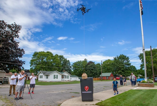 Representatives from DroneDek demonstrate a drone food delivery to a secure box prototype on Thursday, Aug. 26, 2021, in Lakeville.