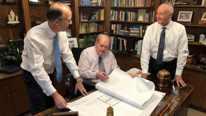 Dr. Michael C. Blackwell, center, is joined by, left to right, Jay Westmoreland and BCH's COO Keith Henry to discuss architect drawings for one of the three homes to be built at River Hill Refuge in Shelby.