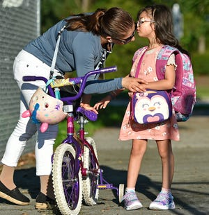"""First-grader, Charlotte Marlass, 6, kisses her mom, Marisol Marlass goodbye before her first day of school at Gilbert W McNeal Elementary School, located in Manatee County, FL. Her mother stated, """"she has a mask and I'm leaving it up to her whether she wants to wear it or not. Students returned to school Tuesday (August 10, 2021) morning in Manatee and Sarasota counties, and for many it was the first time attending school without a mask on in more than a year. THOMAS BENDER/ SARASOTA HERALD-TRIBUNE"""