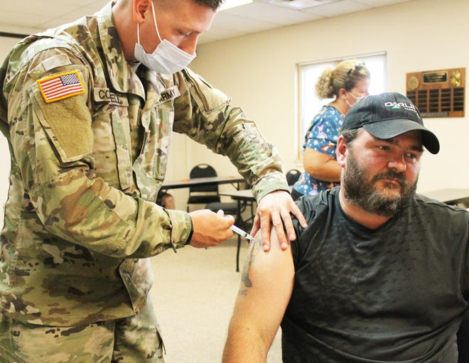 Cpl. Charles Colwell of the National Guard administers a COVID vaccine to Dan Beck on Wednesday in White Pigeon.