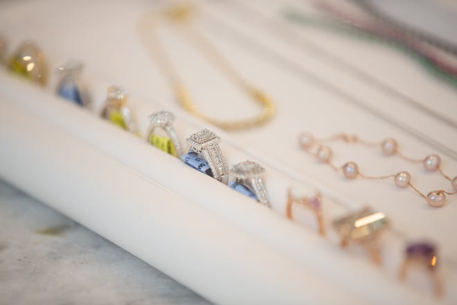 Diamond rings, pearl bracelets and precious gemstone jewelry are laid out on a countertop at MB Addis & Co. Legacy Jewelers.