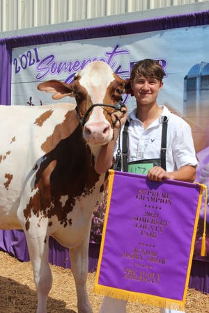 Aidan Ream, 16, won Supreme Champion during the Dairy Show sponsored by the Daily American at the Somerset County Fair on Wednesday with his junior three-year-old red-and-white cow named Charity.