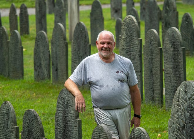 Harry F. Klane photographs gravestones in Worcester's Hope Cemetery on Tuesday.