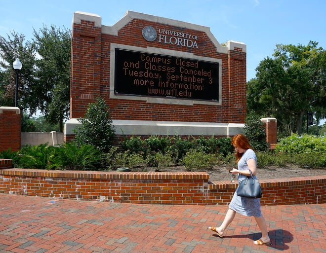A woman walks past a University of Florida welcome sign on the UF campus off University Ave., in Gainesville, Fla. September 5, 2019.  [Brad McClenny/The Gainesville Sun]
