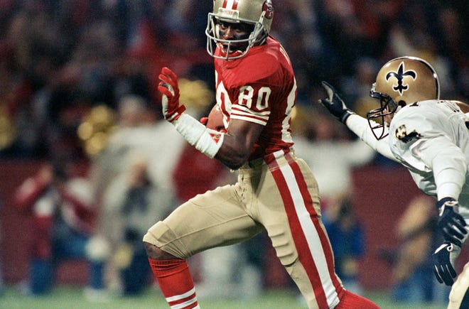 FILE - In this Nov. 7, 1989, file photo, San Francisco 49ers wide receiver Jerry Rice runs past New Orleans Saints' Toi Cook for a touchdown during an NFL football game at Candlestick Park in San Francisco. Known for tireless work ethic even in late stages of career, Rice holds virtually every significant receiving mark, including most career receptions (1,549); yards receiving (22,895); total touchdowns (208); and combined net yards (23,546). (AP Photo/Martha Jane Stanton, File)