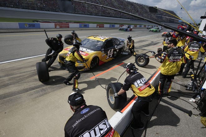 The crew on Chase Briscoe's No.14 Cummins Ford Mustang springs into action during a pit stop Sunday at Michigan International Speedway.