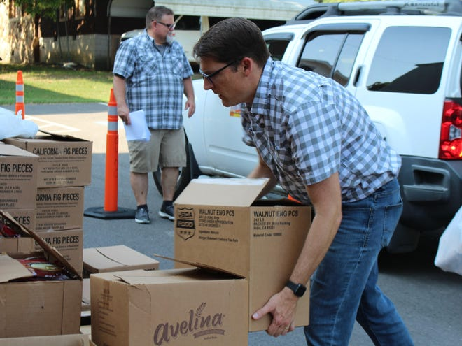 Senior Pastor John Embrey prepares to place a U.S. Department of Agriculture commodity box in a vehicle during the Aug. 26 distribution at Greenwood United Methodist Church.