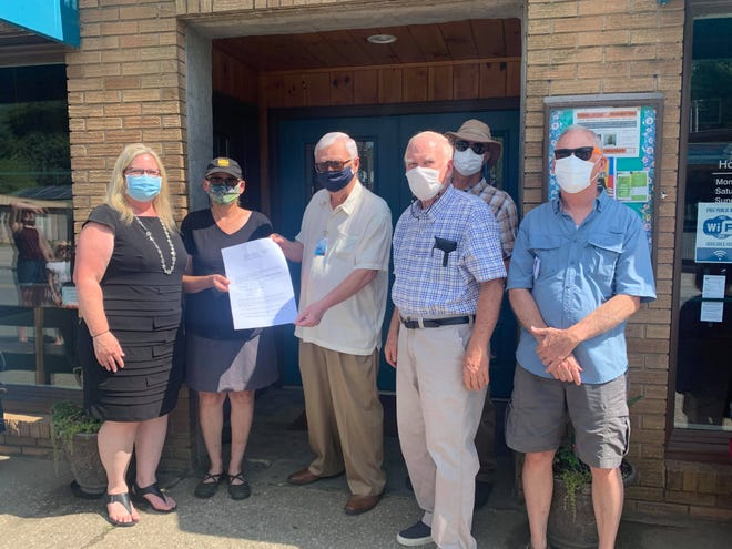 Members of Friends of Hot Springs Library (FHSL) celebrated the organization's paying back its debt owed to the commissioners for down payment at its Bridge Street location on Aug. 12.