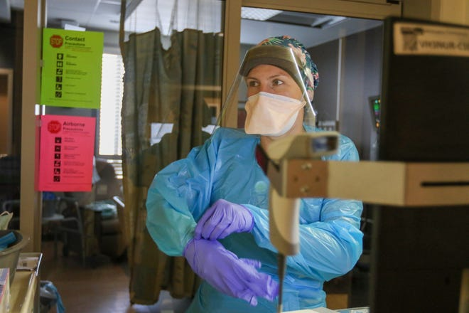 A nurse dons protective gear before attending to a patient.