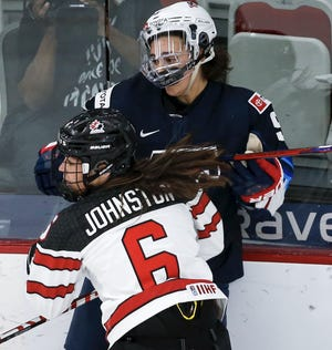 Farmington Hills' Megan Keller, top, is checked by Canada's Rebecca Johnston during the first period at the women's world hockey championships on Thursday in Calgary, Alberta.