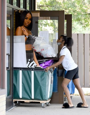 Alexis Knowles of Detroit pushes a cart full of belongings, including a life size cutout of her sister Asia, into Putnam Hall during Eastern Michigan University's move in day in Ypsilanti, Thursday, August 26, 2021.