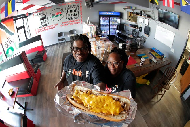 Roderick and Fay Godwin, owners of The Jerk Joint, show off their sizeable jerk chicken sandwich.